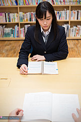 Student Reading Book In Library Wearing Uniform
