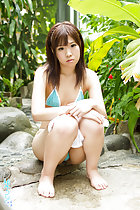 Sitting in leafy garden in tiny bikini bare feet planted on floor