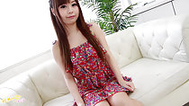 Cute Japanese teen Mikuru sitting on couch wearing summer dress long hair down over her chest holding hem of dress over her thighs