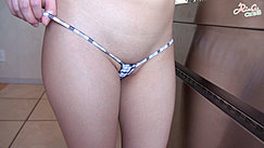 Rinay Standing On Tiled Floor Pulling On Thong Panties Over Her Shaved Pussy