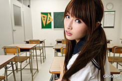 Seated At Her Desk Looking Over Her Shoulder Long Hair In Pigtails