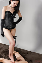 Wearing black bodice and gloves in garter bare foot on naked mans thigh long hair