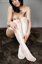 Seated with legs raised hands on her white stockings