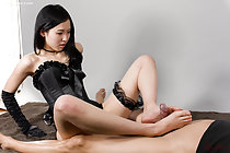 Sitting down long hair over her shoulder in bodice and gloves black garter on her left thigh giving footjob