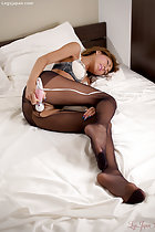 Sugisaki Nanami lying on her side masturbating in ripped pantyhose