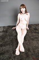 Seated naked on rug big breasts legs crossed bare feet stretched out