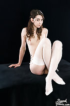 Seated nude knees drawn up wearing stockings