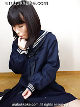 Seated on wooden floor in seifuku uniform sucking her finger